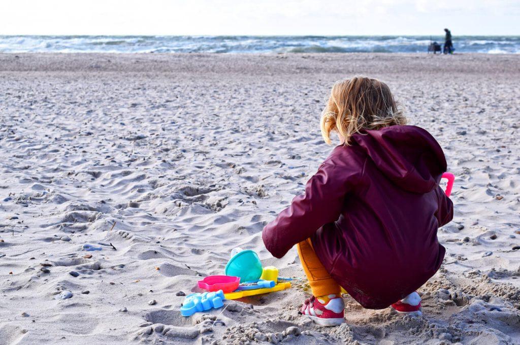 Mae aan het spelen in Henne strand