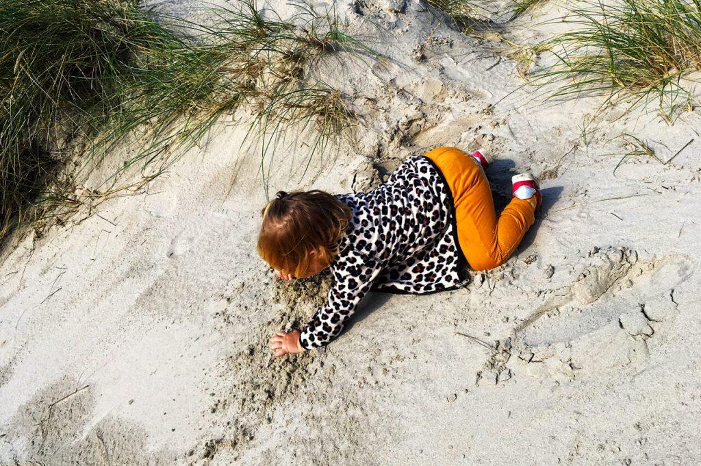 Mae aan het spelen in het zand van Henne Strand
