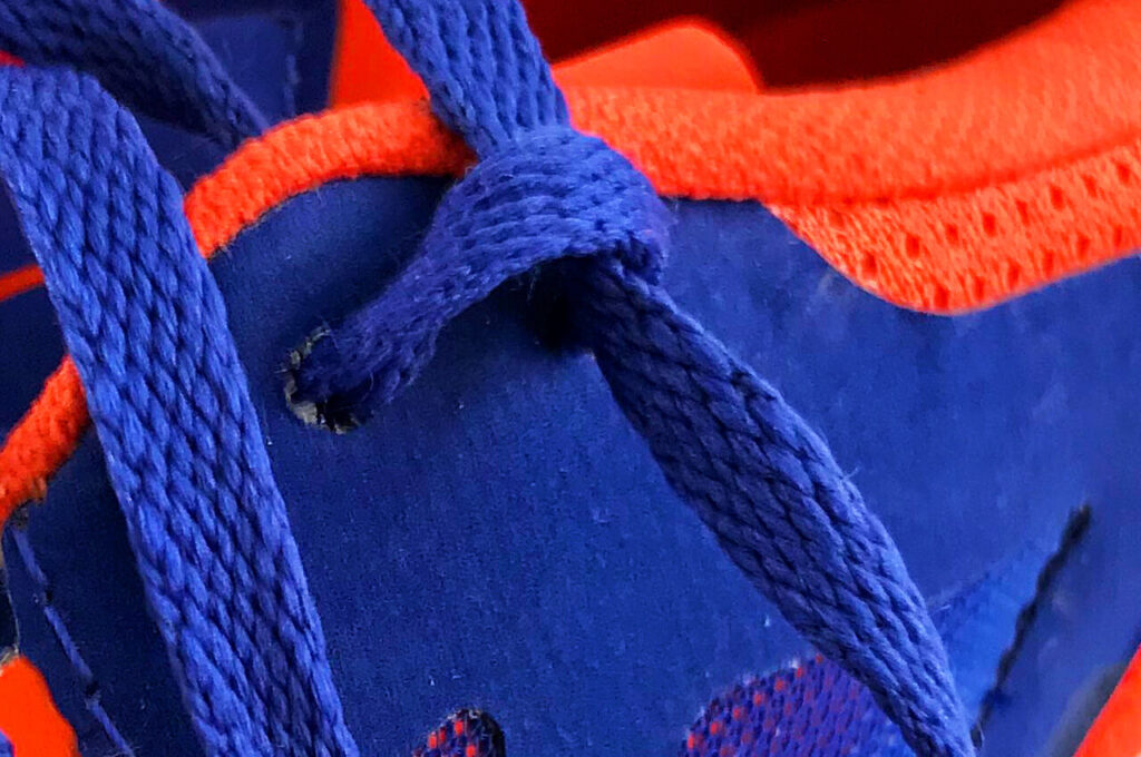 De lus van de veters van de hardloopschoen