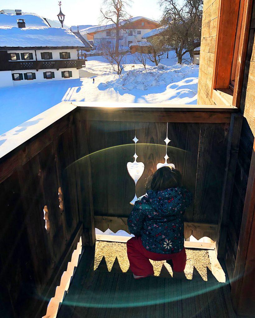 Mae kijkt door een gat op het balkon naar de sneeuw